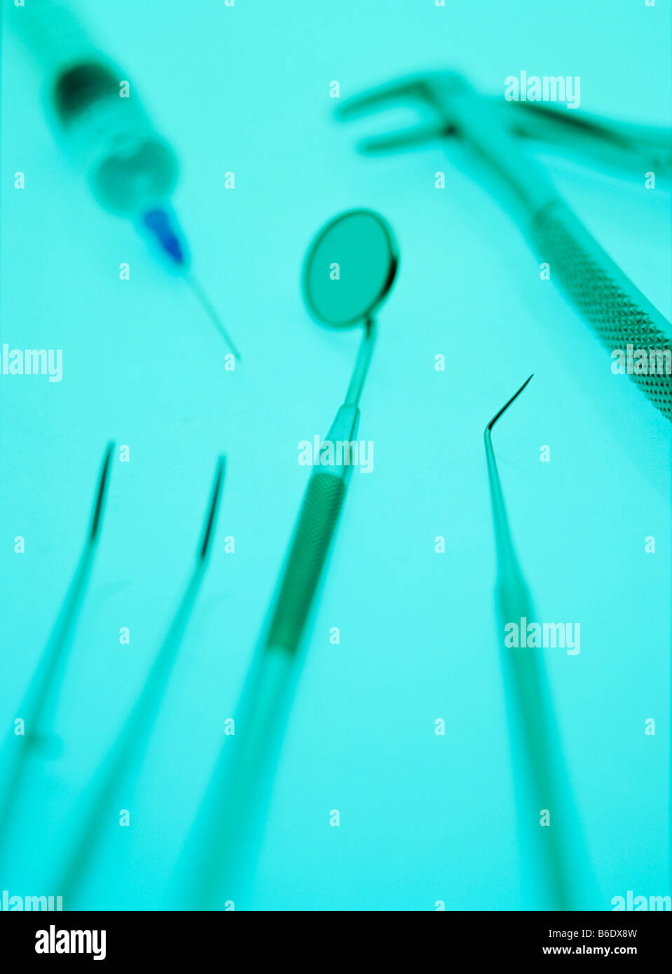 Dental equipment. At centre is an angled mirror for viewing the teeth. A pair of tweezers is at lower left. - Stock Image