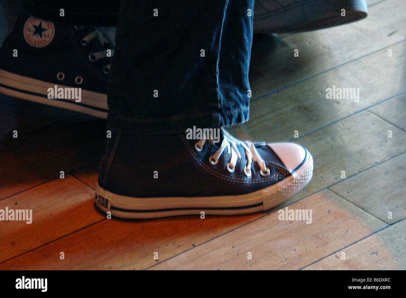0f08d9f5cb6 Indoor Scene of a Person s Feet Wearing Black Converse Chuck Taylor High  Top Basketball Sneakers and