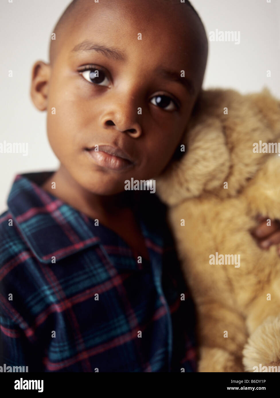 Boy with teddy bear.4 year old boy smiling and holding a teddy bear.Cuddly toys can provide a child with companionship. - Stock Image