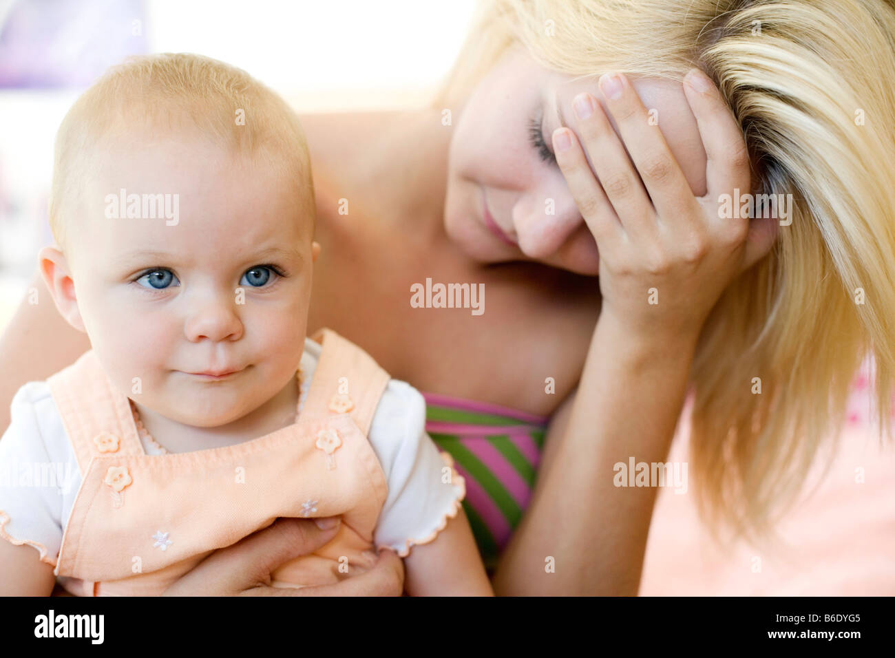 Teenage mother and baby. Stressed young mother holding her 10 month old daughter. Posed by models. - Stock Image