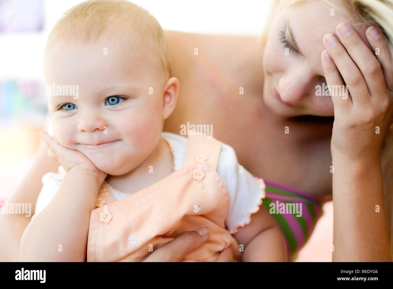 Teenage mother and baby. Stressed young mother holding her 10 month old daughter. Posed by models. Stock Photo