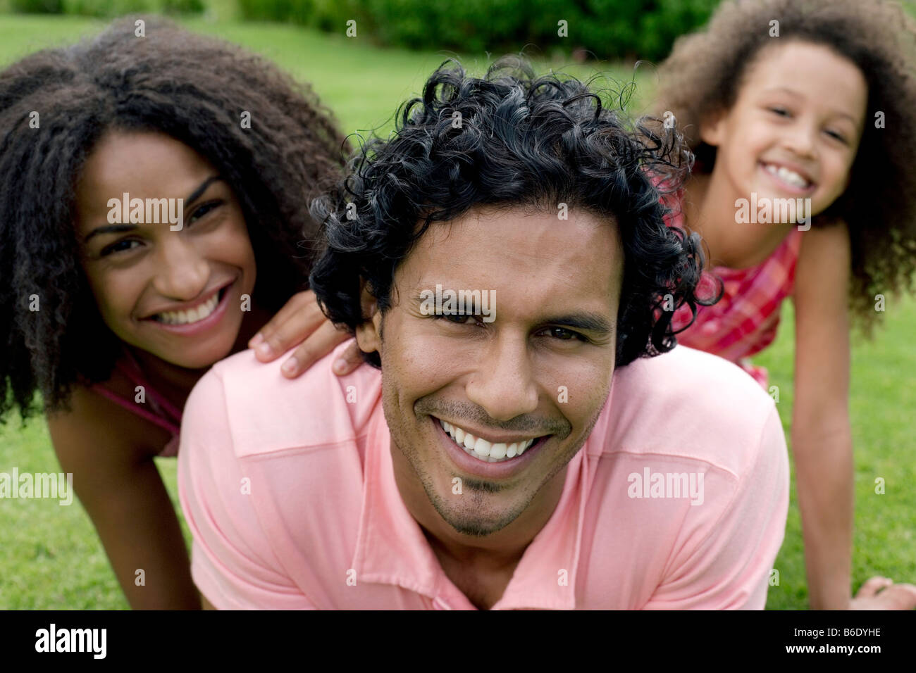 Happy family. Parents with their daughter on the grass. Stock Photo