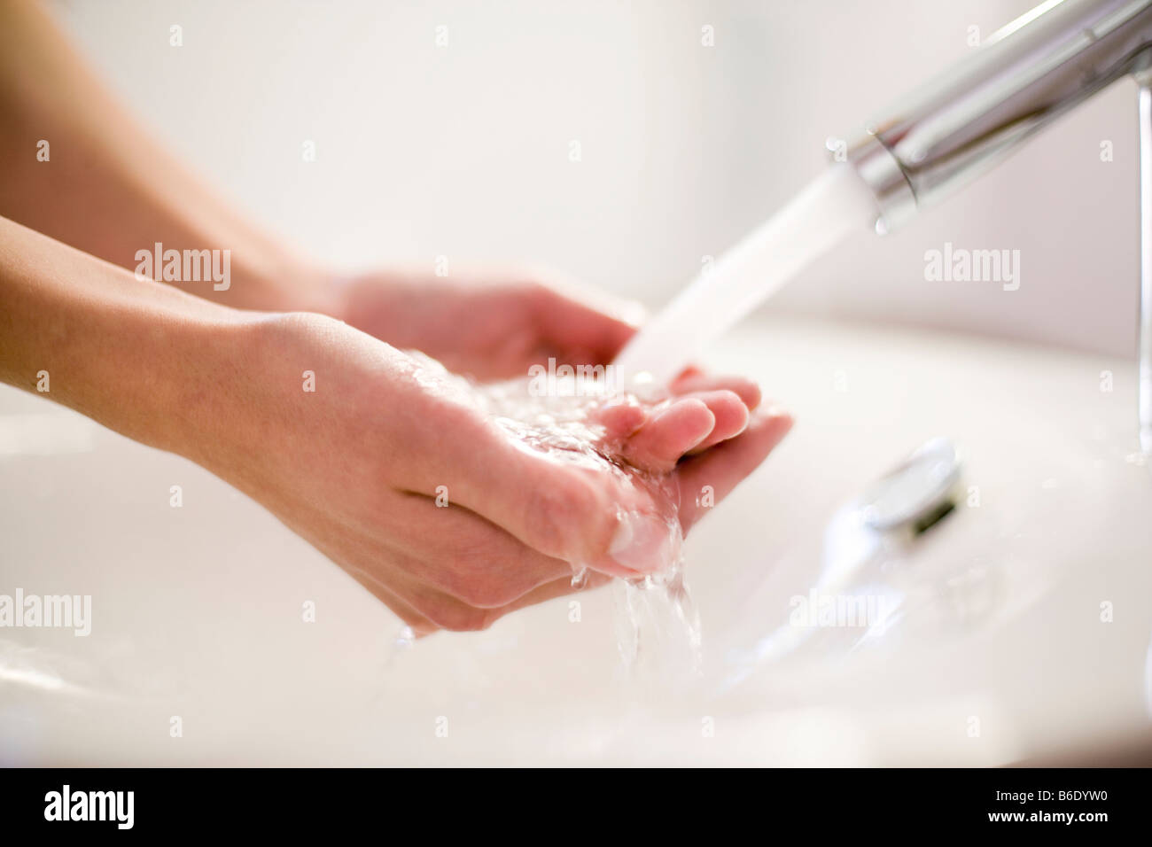 Washing hands under running water from a tap. - Stock Image
