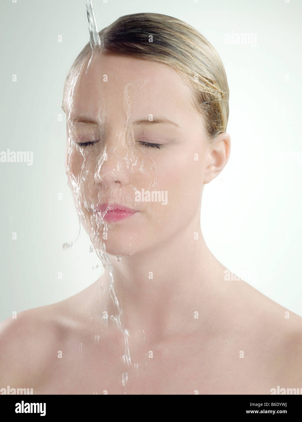 Woman with wet skin. Woman with water pouring down her face. - Stock Image