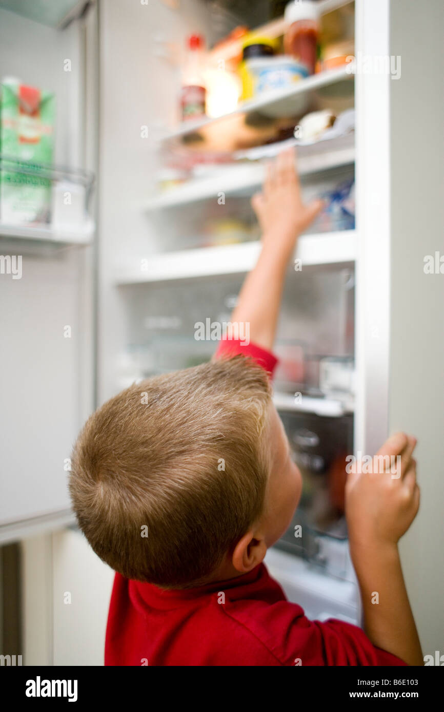 Boy looking in fridge and grabbing an item of food. - Stock Image