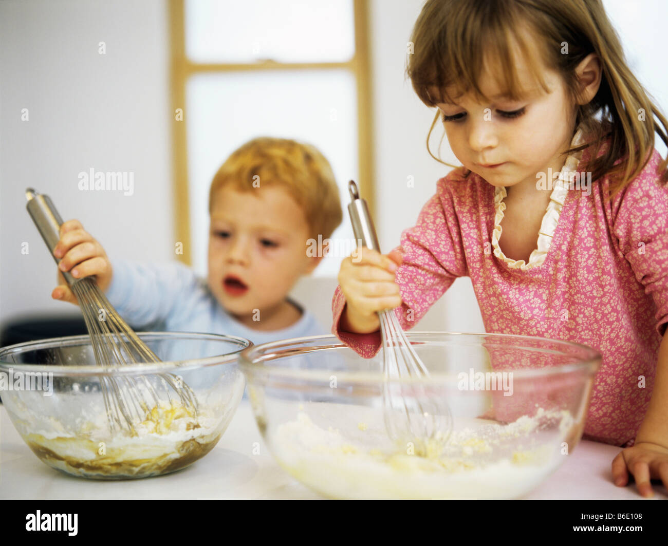 Making cakes. Two three year old children mixing eggs, sugar and flour in a mixing bowl. - Stock Image
