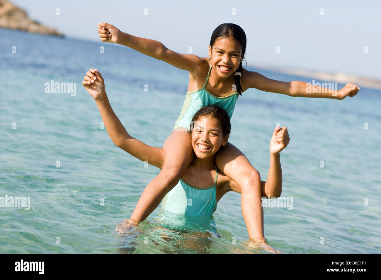 Sisters on holiday. Girl sitting on her sister's shoulders in the sea. - Stock Image