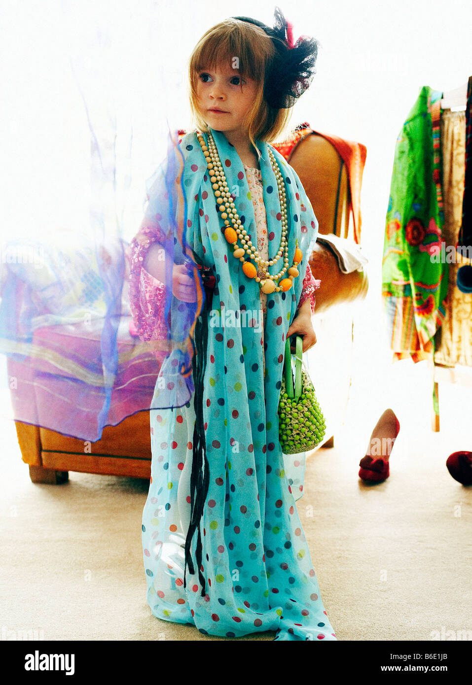 Dressing up. Four year old girl playing dressing up games. - Stock Image