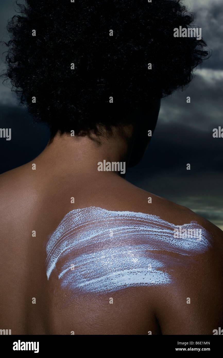 Sun protection. Sun cream on a man's shoulder. - Stock Image