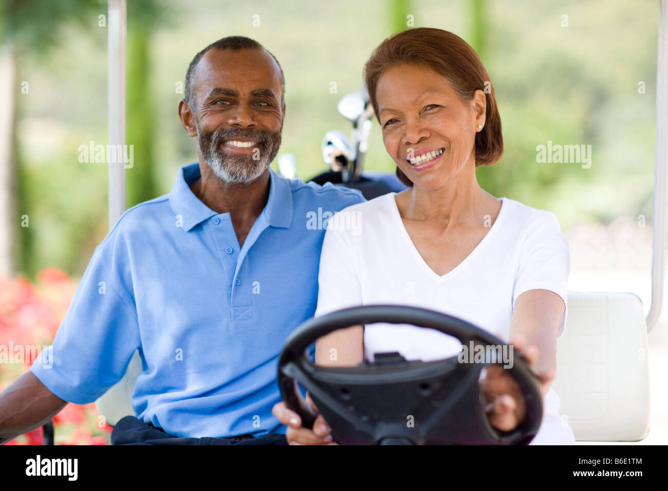 Golf players. Husband and wife using a golf cart during a round of golf. - Stock Image