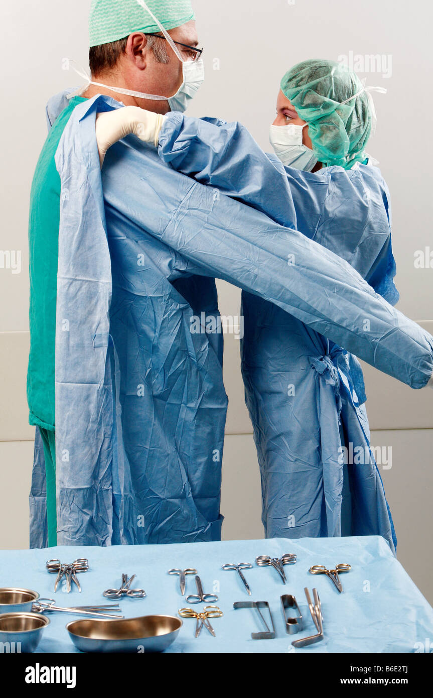 Preparing for surgery. Surgeons putting on scrubs to prevent contamination during surgery - Stock Image