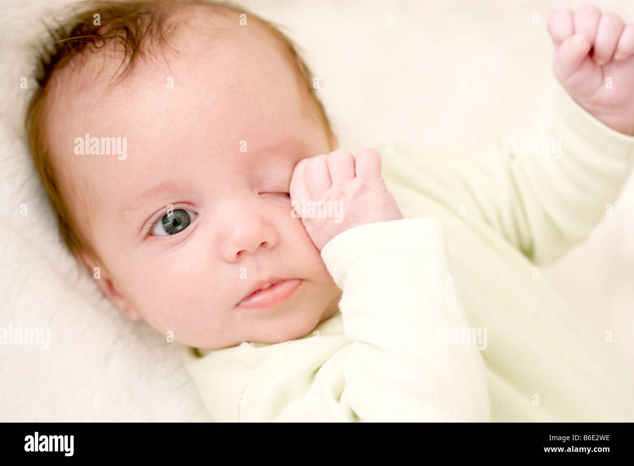 Tired baby girl rubbing her eye - Stock Image