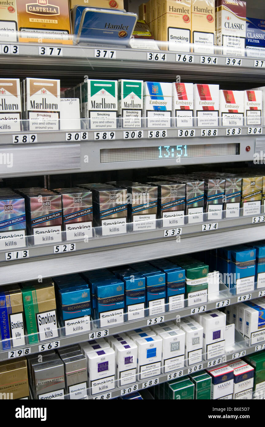 cigarettes cigarette selling shop display fag fags tobacco corner packet health warning public cancer related death - Stock Image