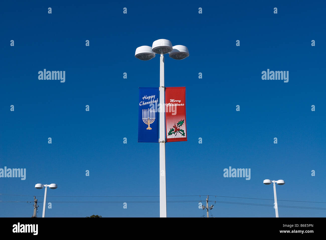 street lights with flags displaying Happy Chanukkah/Merry Christmas greetings - Stock Image