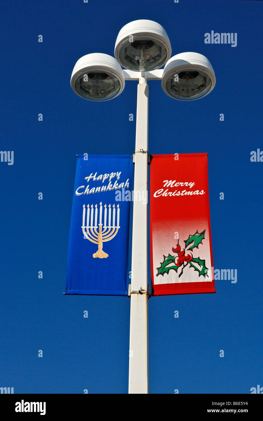 parking lights with flags displaying Happy Chanukkah/Merry Christmas greetings - Stock Image