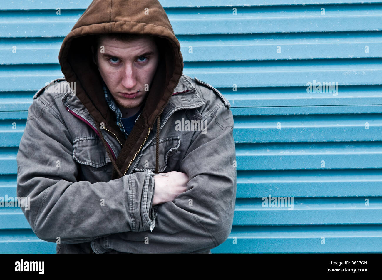 Young man wearing a hooded jacket alone and isolated huddled up looking withdrawn - Stock Image