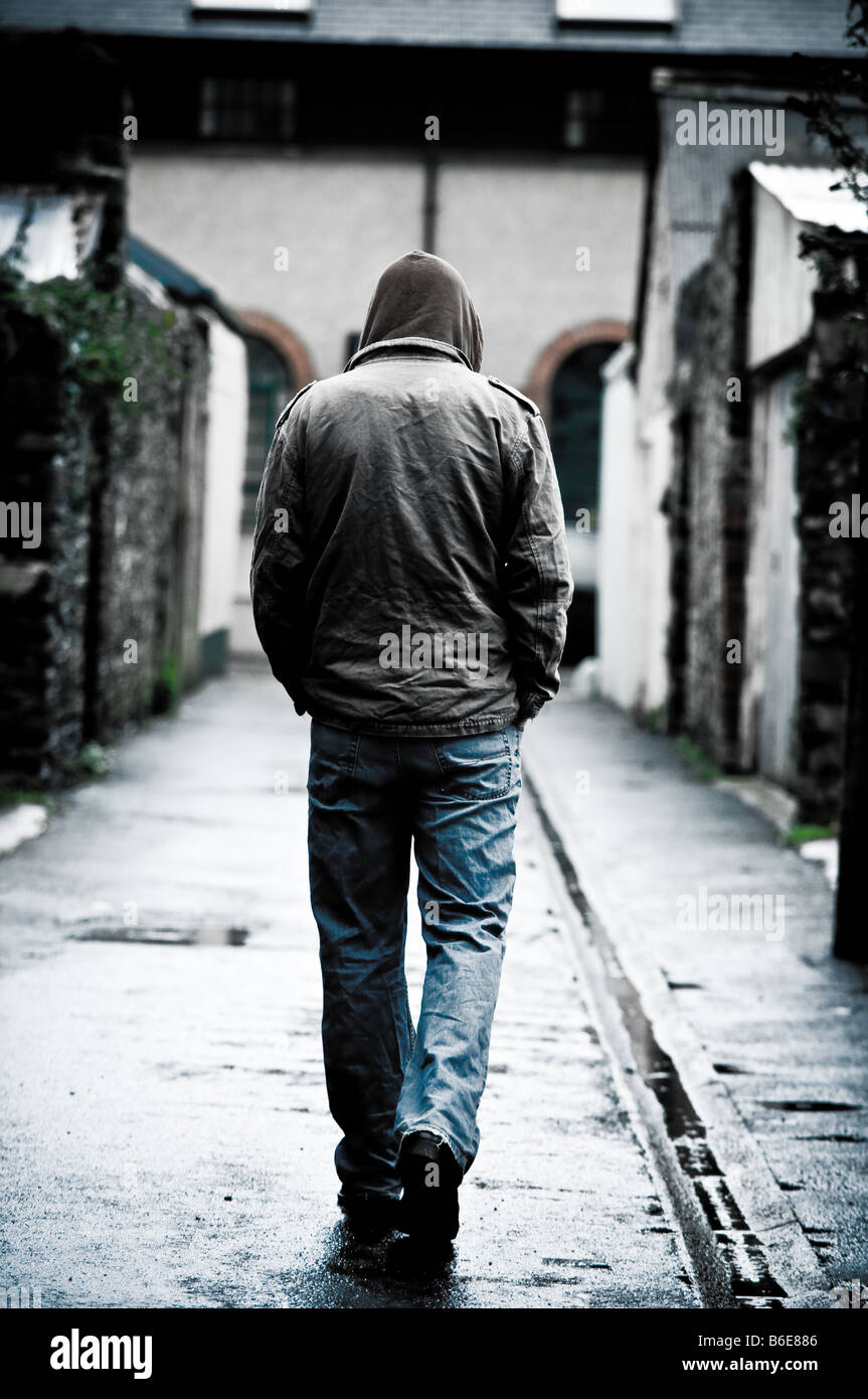 Young man wearing a hooded jacket alone and isolated walking down an alleyway in a city UK seen from behind walking - Stock Image