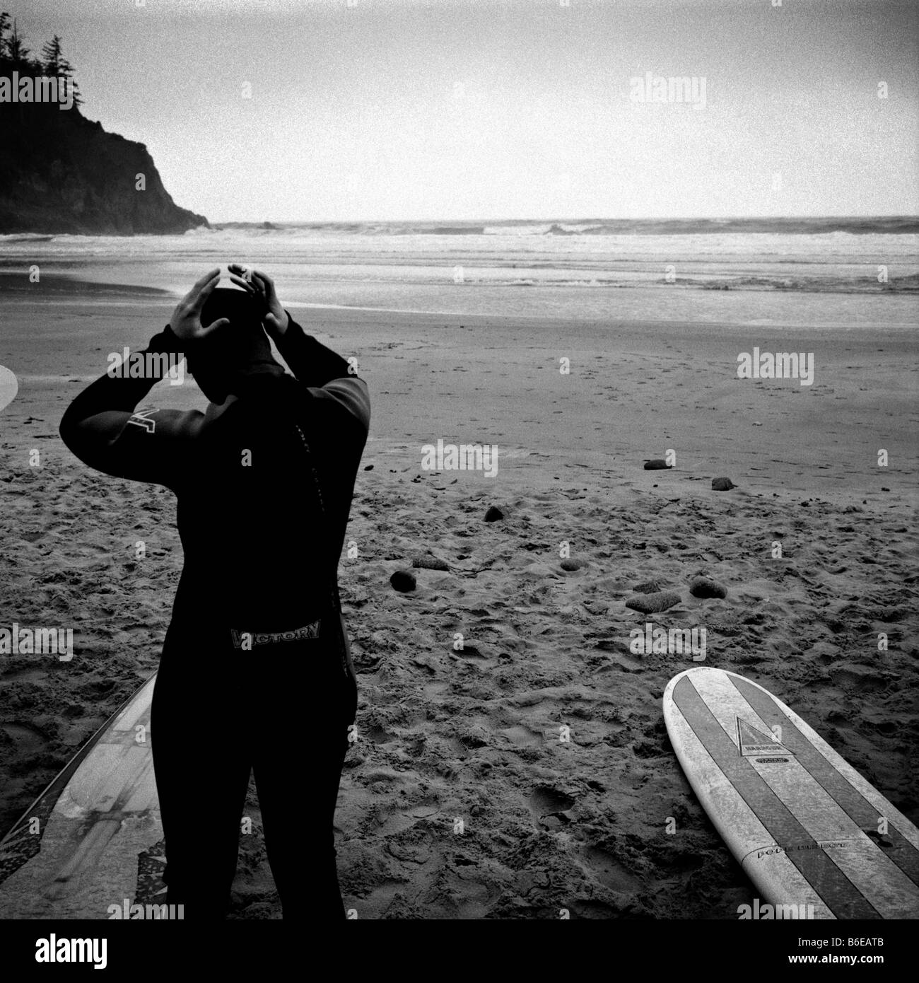 A surfer adjusts his wetsuit before going out at Short Sands Beach, in Oregon. - Stock Image