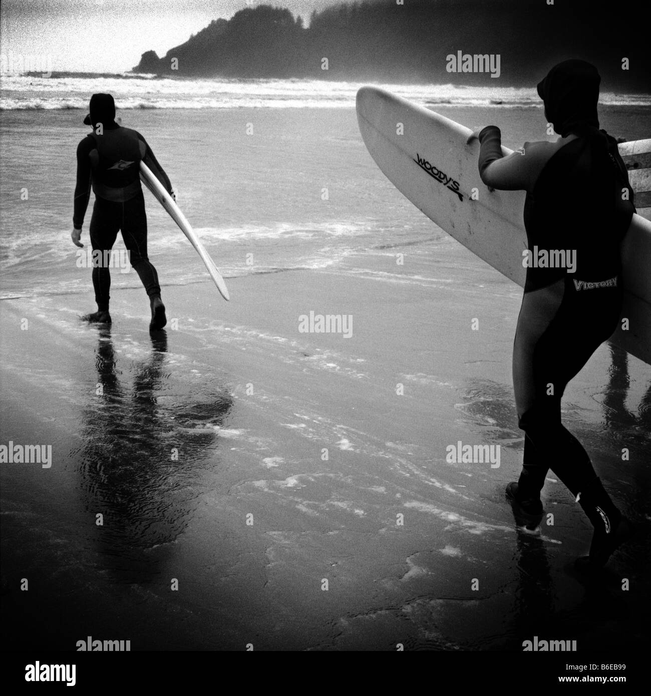 Two surfers head towards the water at Short Sands Beach, in Oregon. - Stock Image
