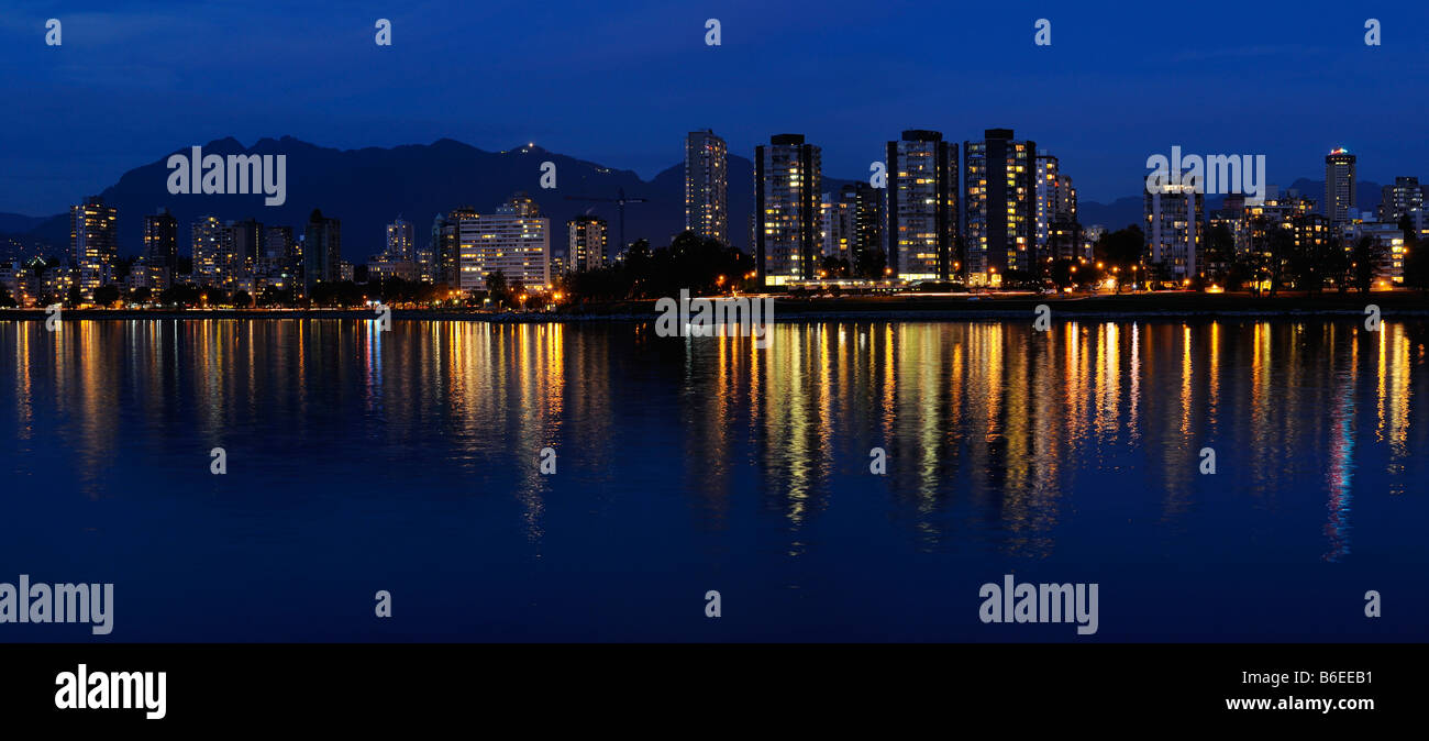Panorama of West End Vancouver skyline city lights at dusk reflected in English Bay with Grouse Mountain British - Stock Image