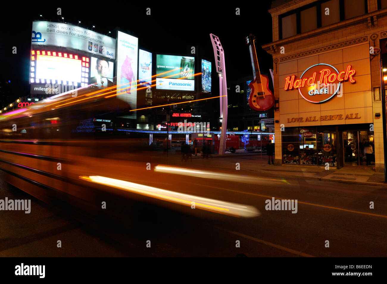 School bus light streaks at night with bright billboards at Dundas Square at Yonge street Toronto - Stock Image