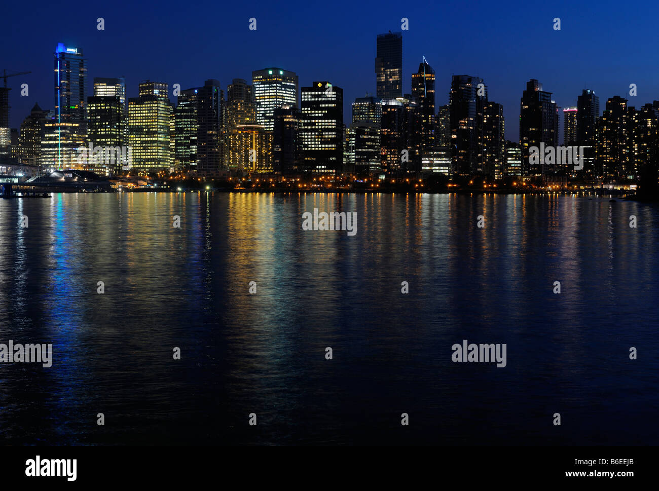 Vancouver skyline cityscape at twilight reflected in Burrard Inlet from Stanley Park - Stock Image