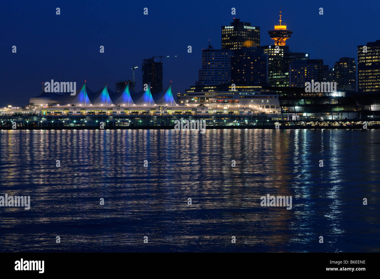 Downtown Vancouver and Canada Place at twilight with city lights reflected in Burrard Inlet British Columbia Canada - Stock Image