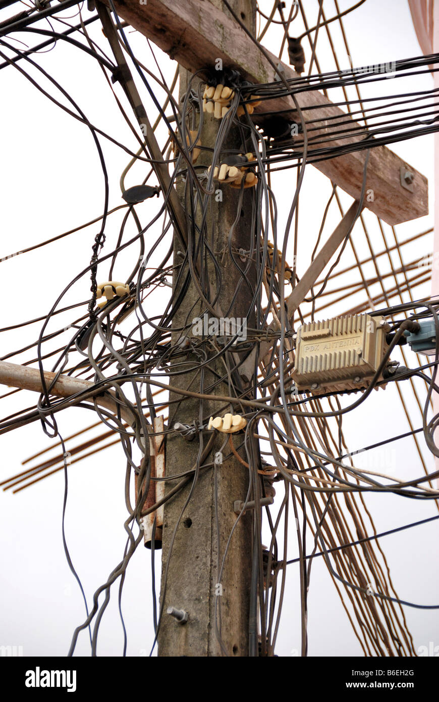 Tangle of telephone and power lines on telegraph pole - Stock Image