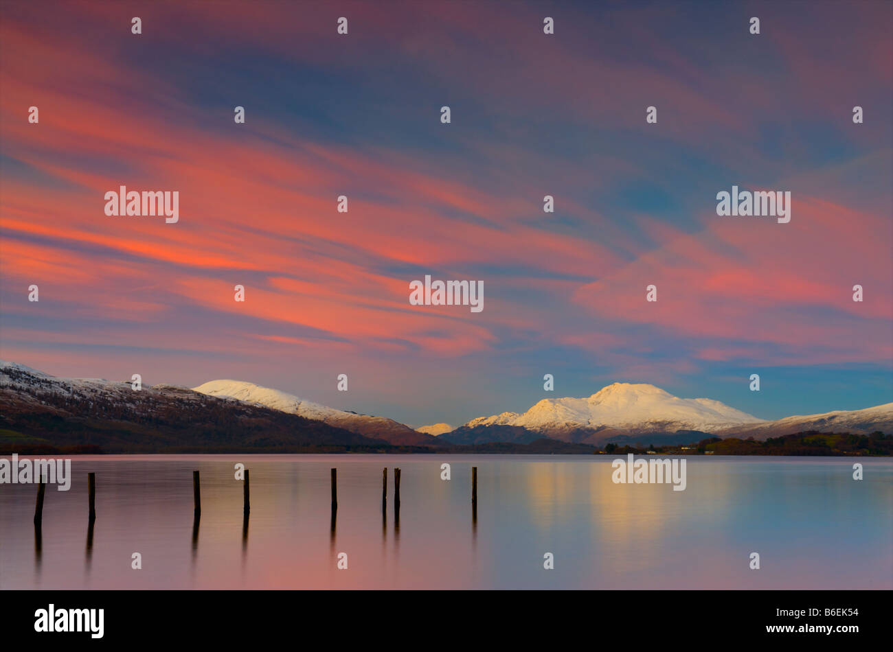 Ben Lomond covered in snow reflecting in Loch Lomond at Dusk. Stock Photo