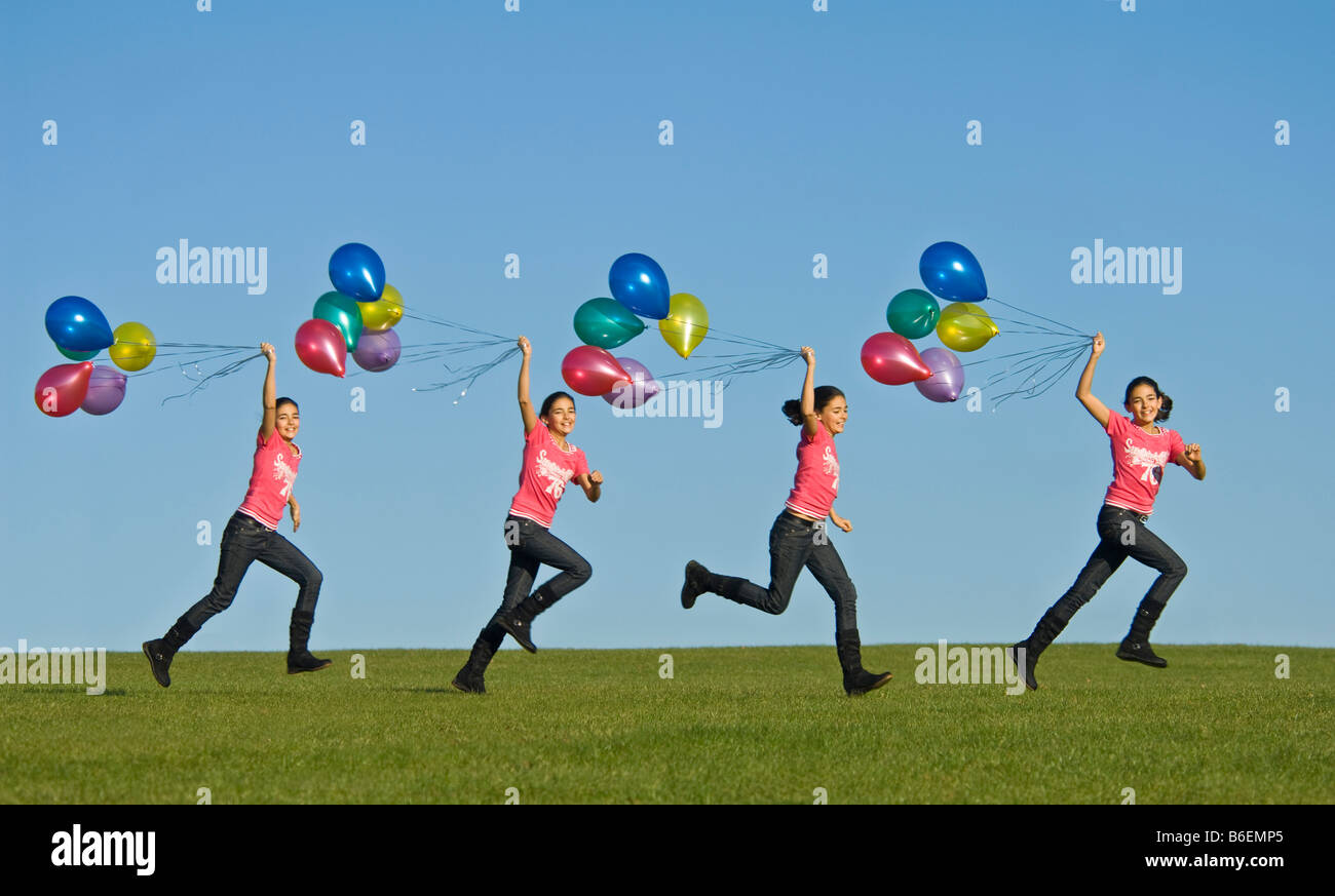 A sequence image of a young girl (11) running happily across green grass with a bunch of balloons trailing behind - Stock Image