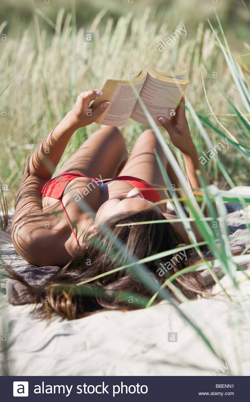 Woman reading in the sand - Stock Image