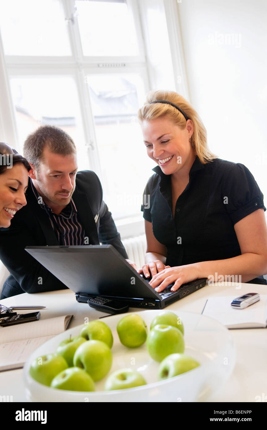 Women and man looking at computer - Stock Image