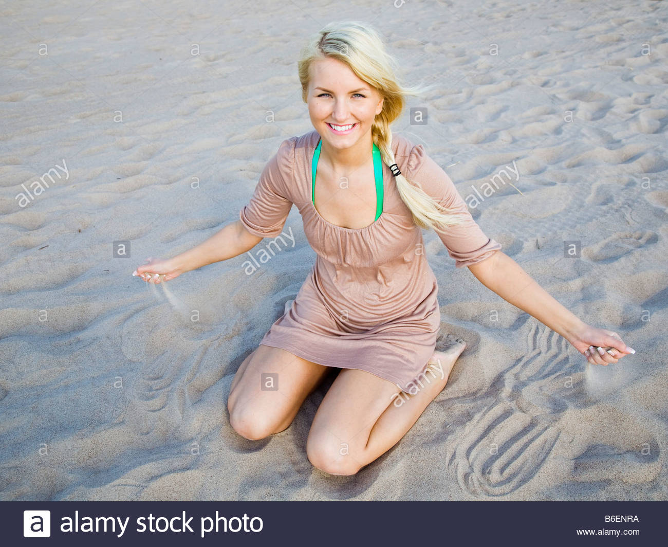 Girl sitting in the sand - Stock Image