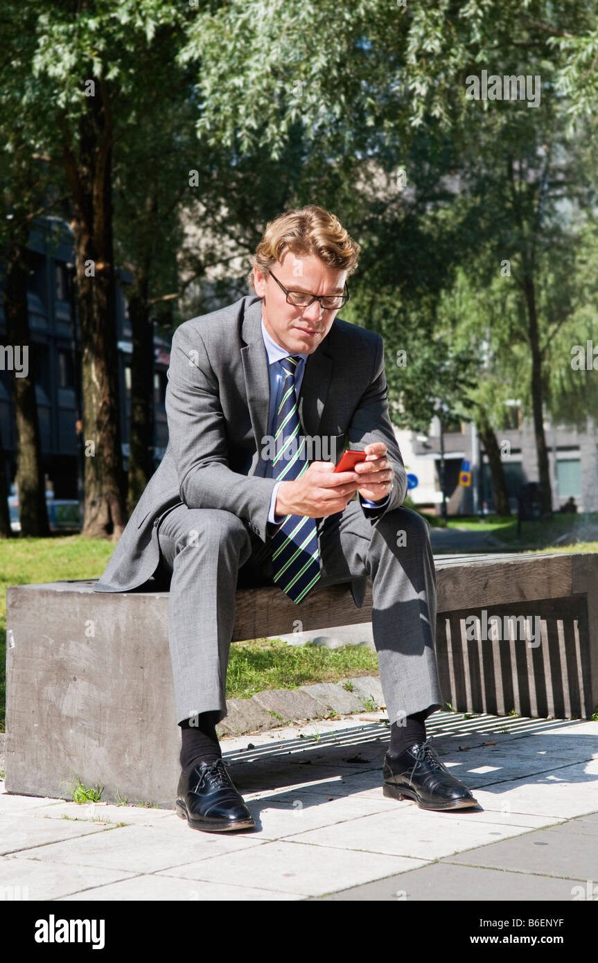 Businessman on bench with cellphone - Stock Image