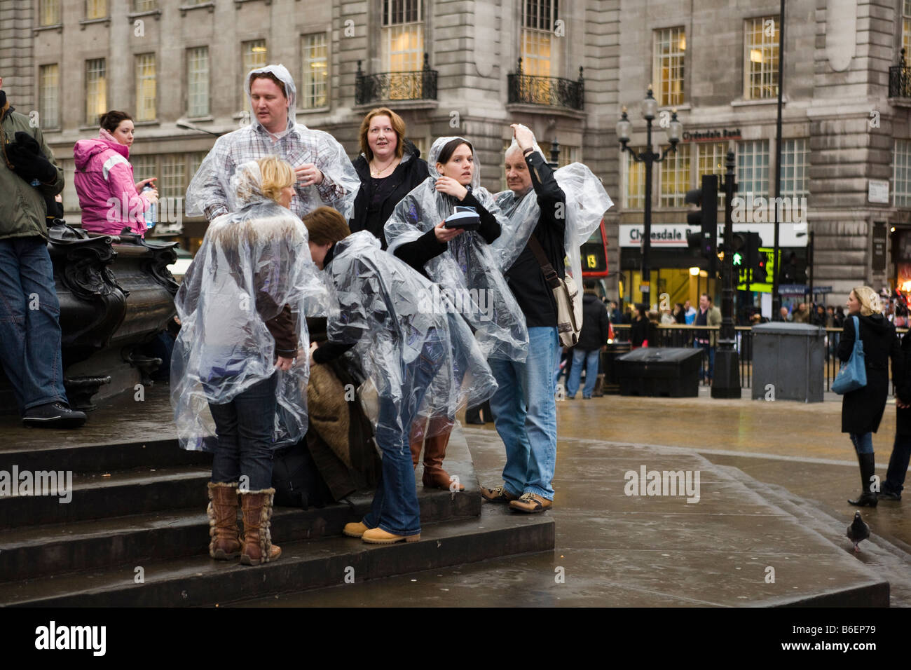 group of tourists in london all wearing the same type of rain coat - Stock Image