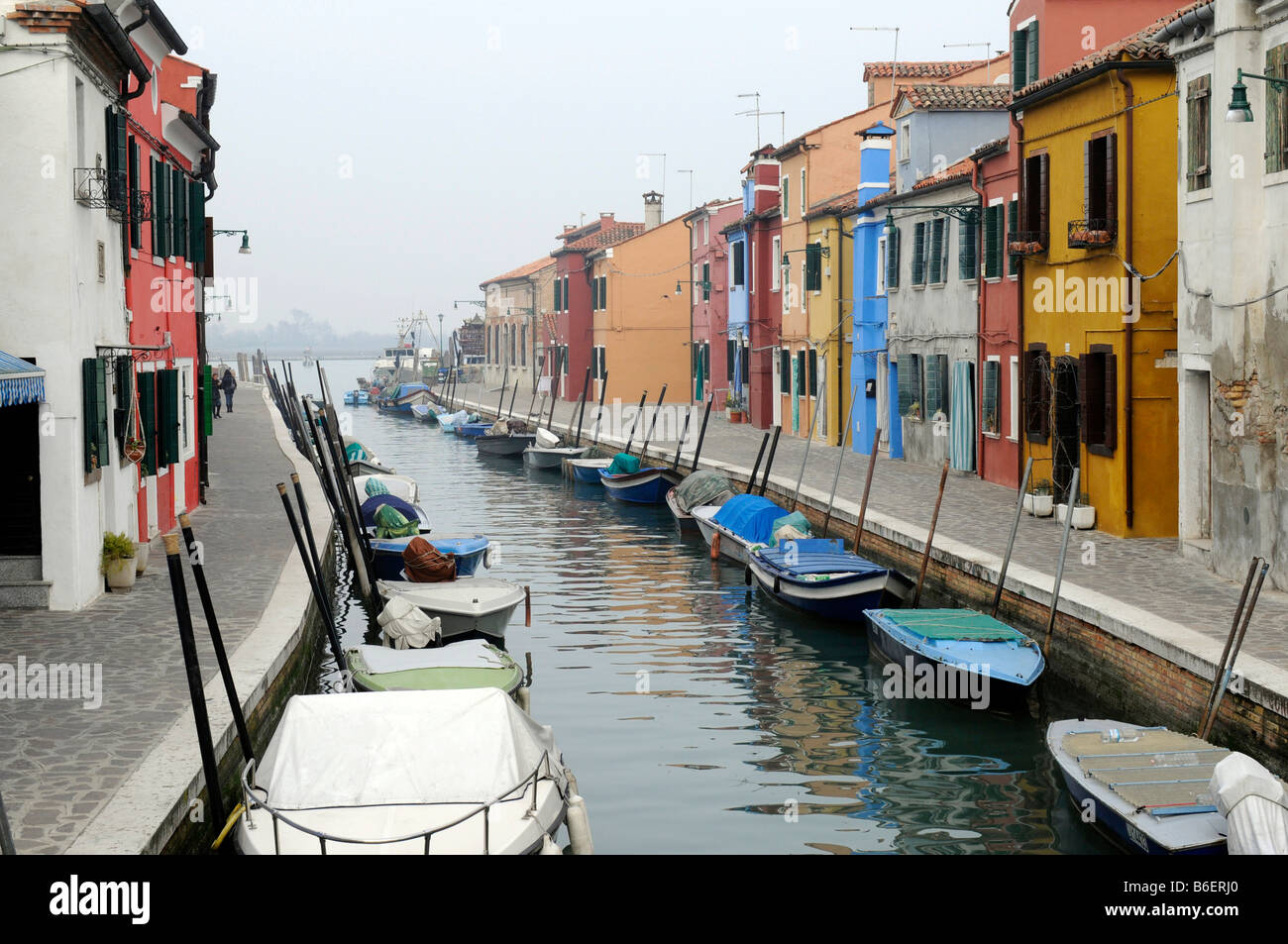Canal lined with boats running between colorfully painted building facades in Burano, Venice, Venetia, Italy, Europe Stock Photo