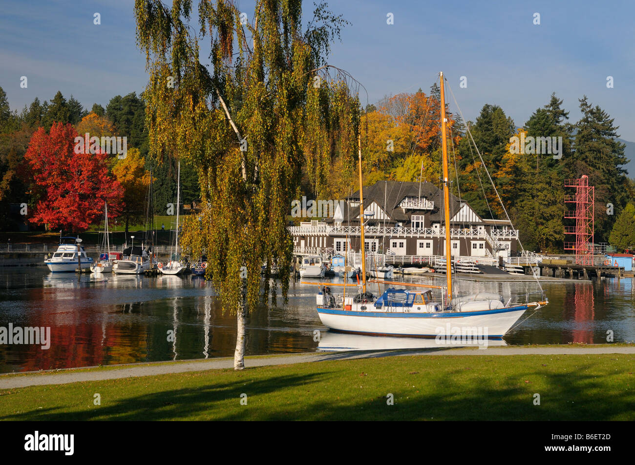 Sailboat cruising out of Coal Harbour at the Vancouver Rowing club in Autumn - Stock Image