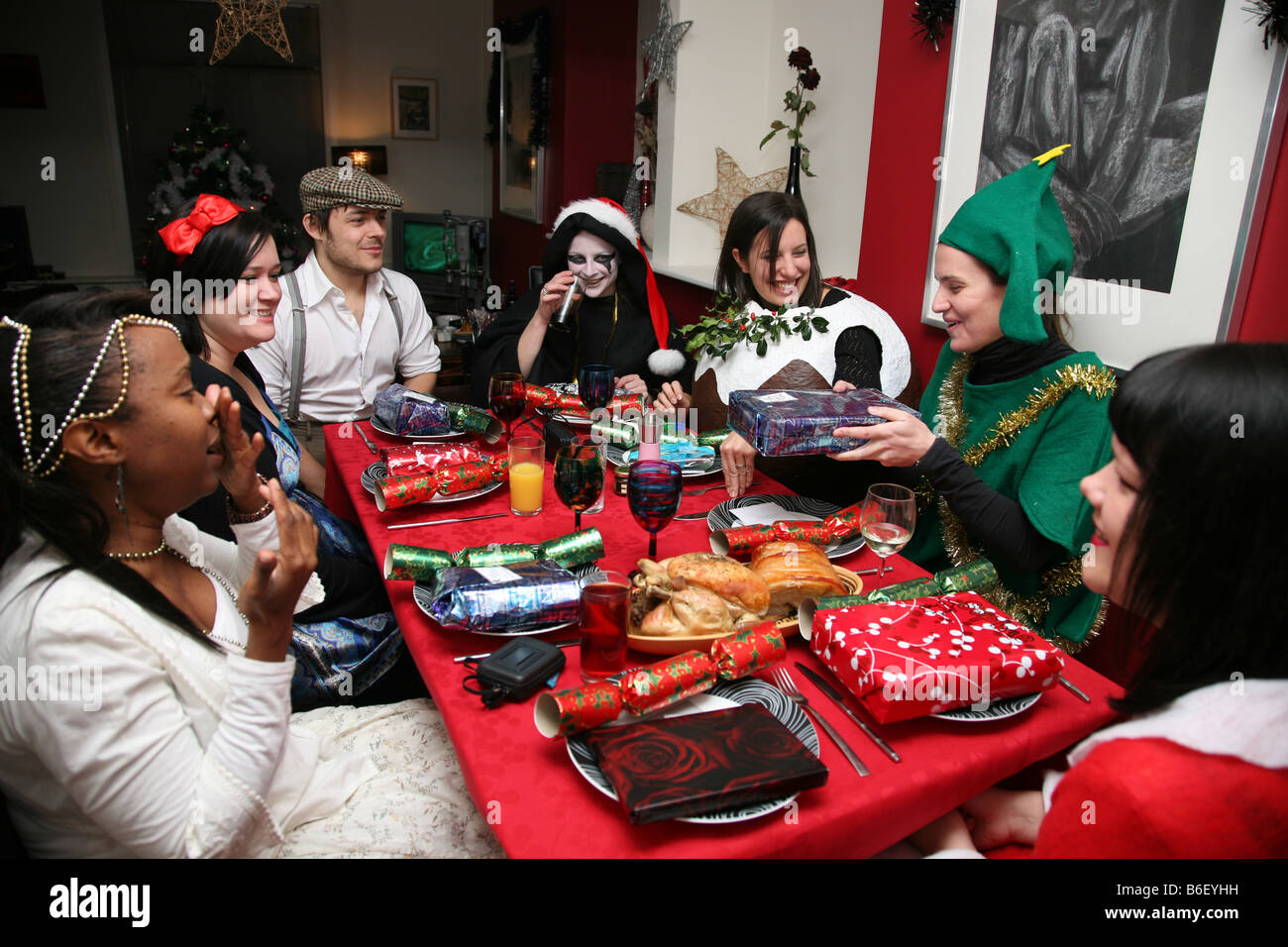 a group of friends having a christmas dinner party stock photo