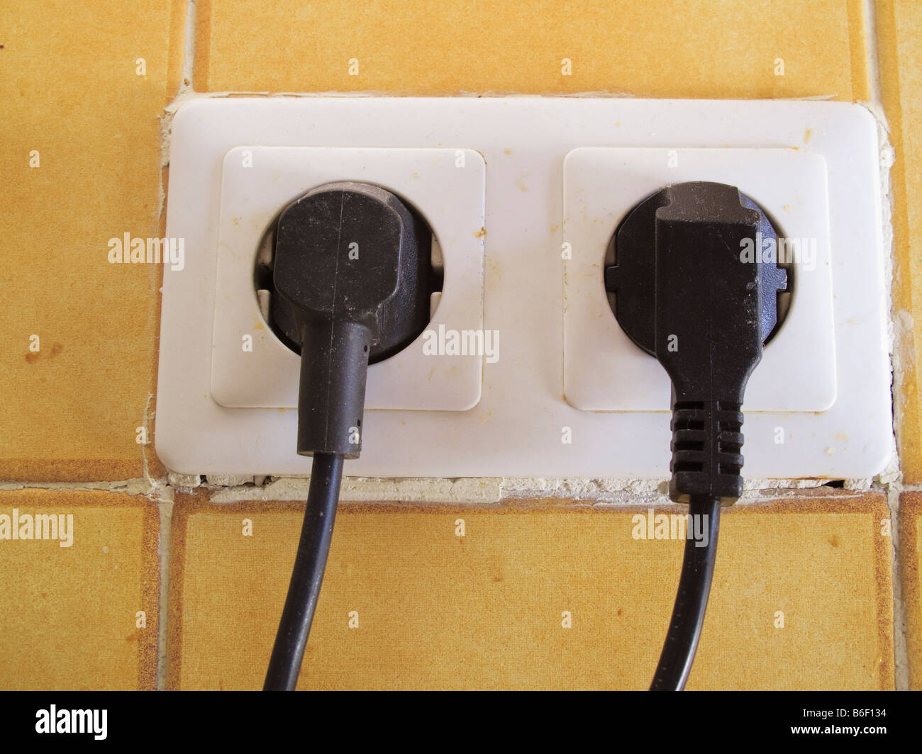 Two electrical plugs plugged into sockets in wall Stock Photo