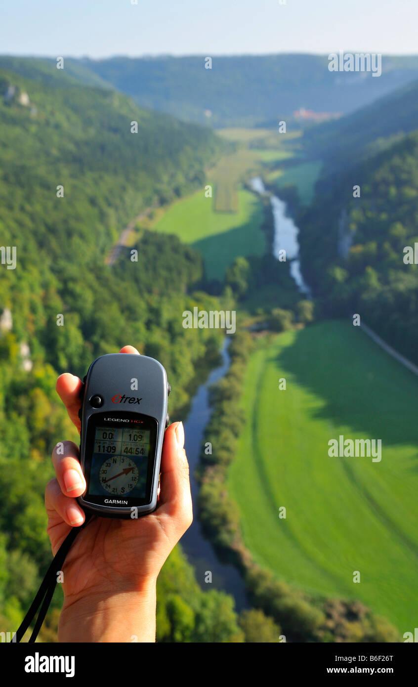 Hand holding a Garmin mobile navigation tool, GPS-navigation, view from Knopfmacherfelsen (button-makers rocks), - Stock Image