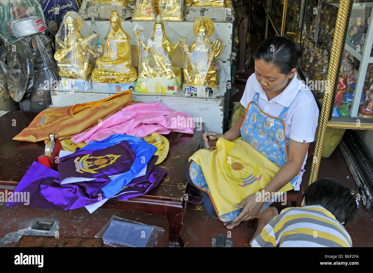 Buddha statue and devotional objects offering for sale in a store, Thailand, Bangkok - Stock Image