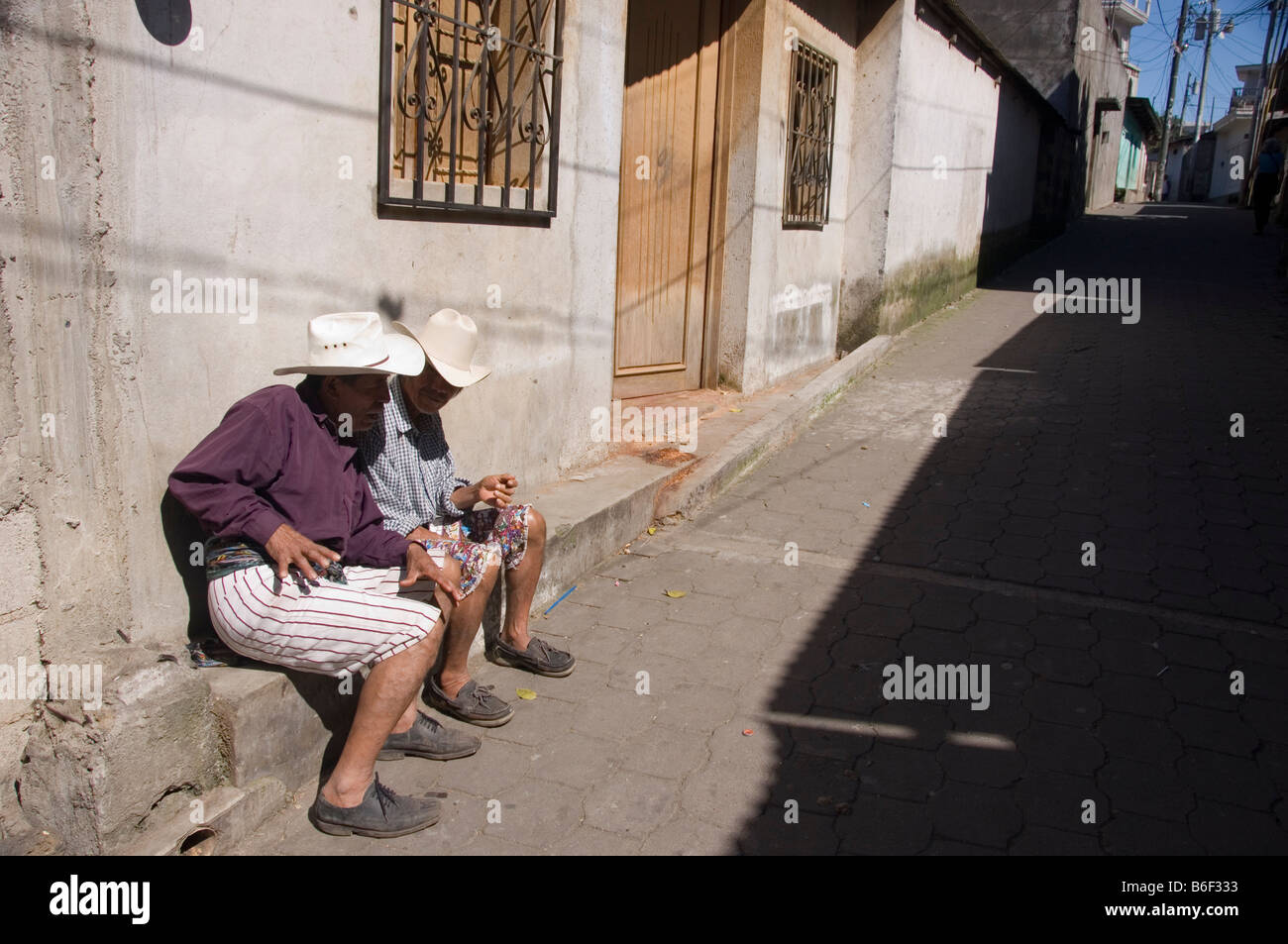 Two men in traditional costume socialising in an alley in Santiago Atitlan, Guatemala. - Stock Image