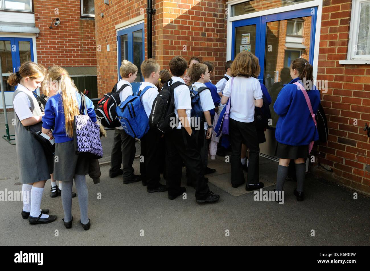 Primary school children wait in playground to enter their school to open - Stock Image