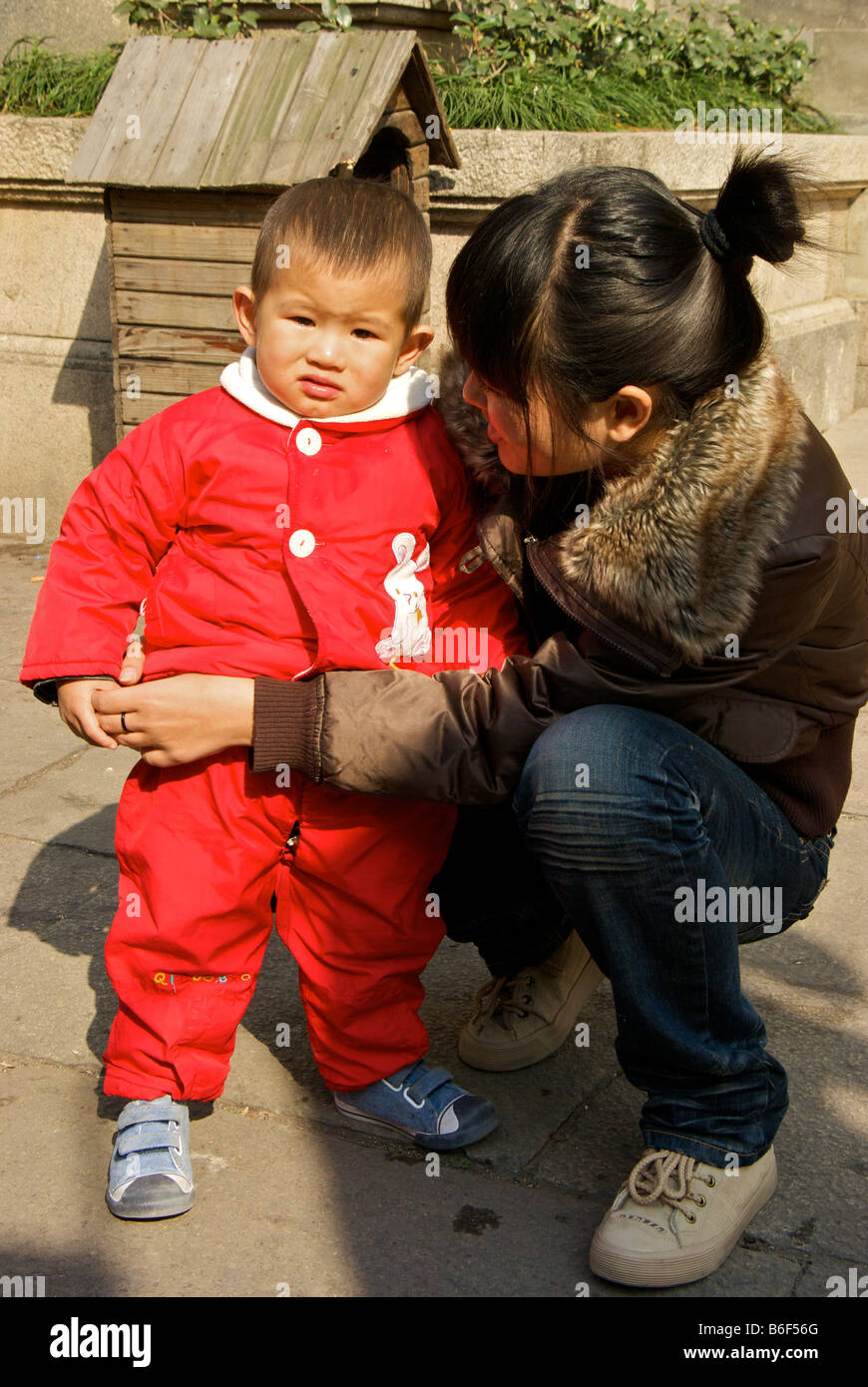 Chinese mother consoling her crying and teary eyed young toddler son on Qilishantang Street - Stock Image