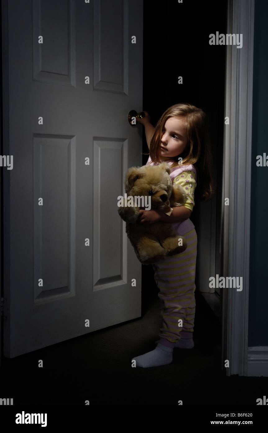 Little girl looking out of a room at night - Stock Image