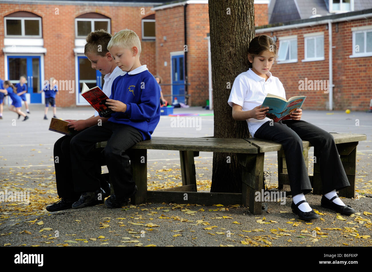Children reading in a primary school playground - Stock Image