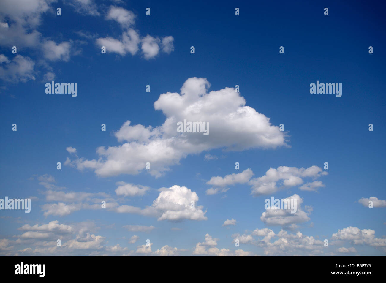 Fluffy white clouds in a blue sky - Stock Image
