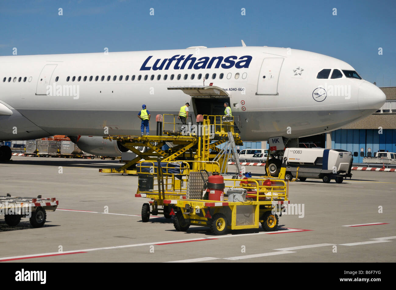 Ground personal on a hydrolic lift loading and unloading a Lufthansa Airlines Airbus A 340 - 600 on the Frankfurt - Stock Image