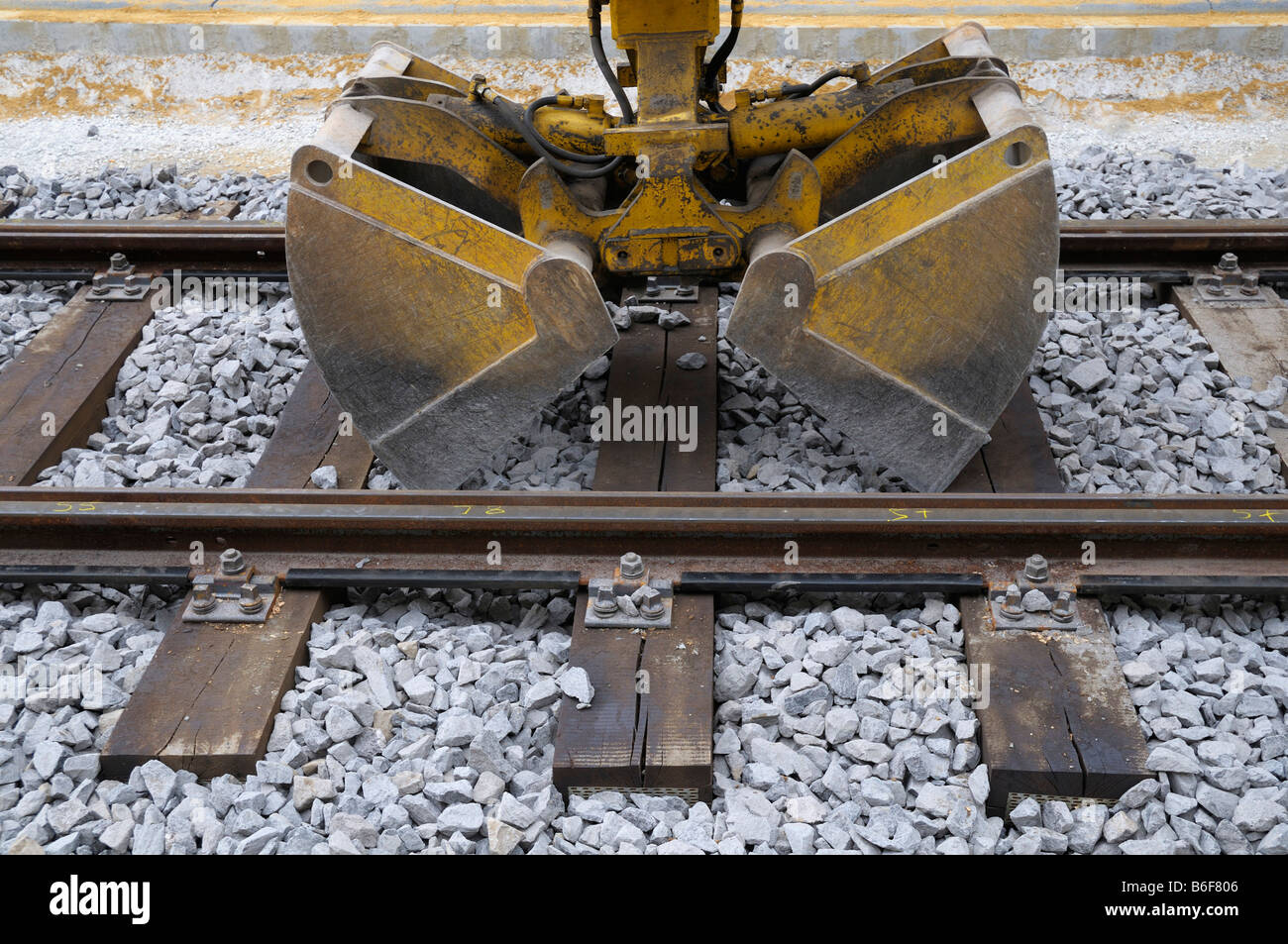 Track construction work, excavator shovel in track bed - Stock Image