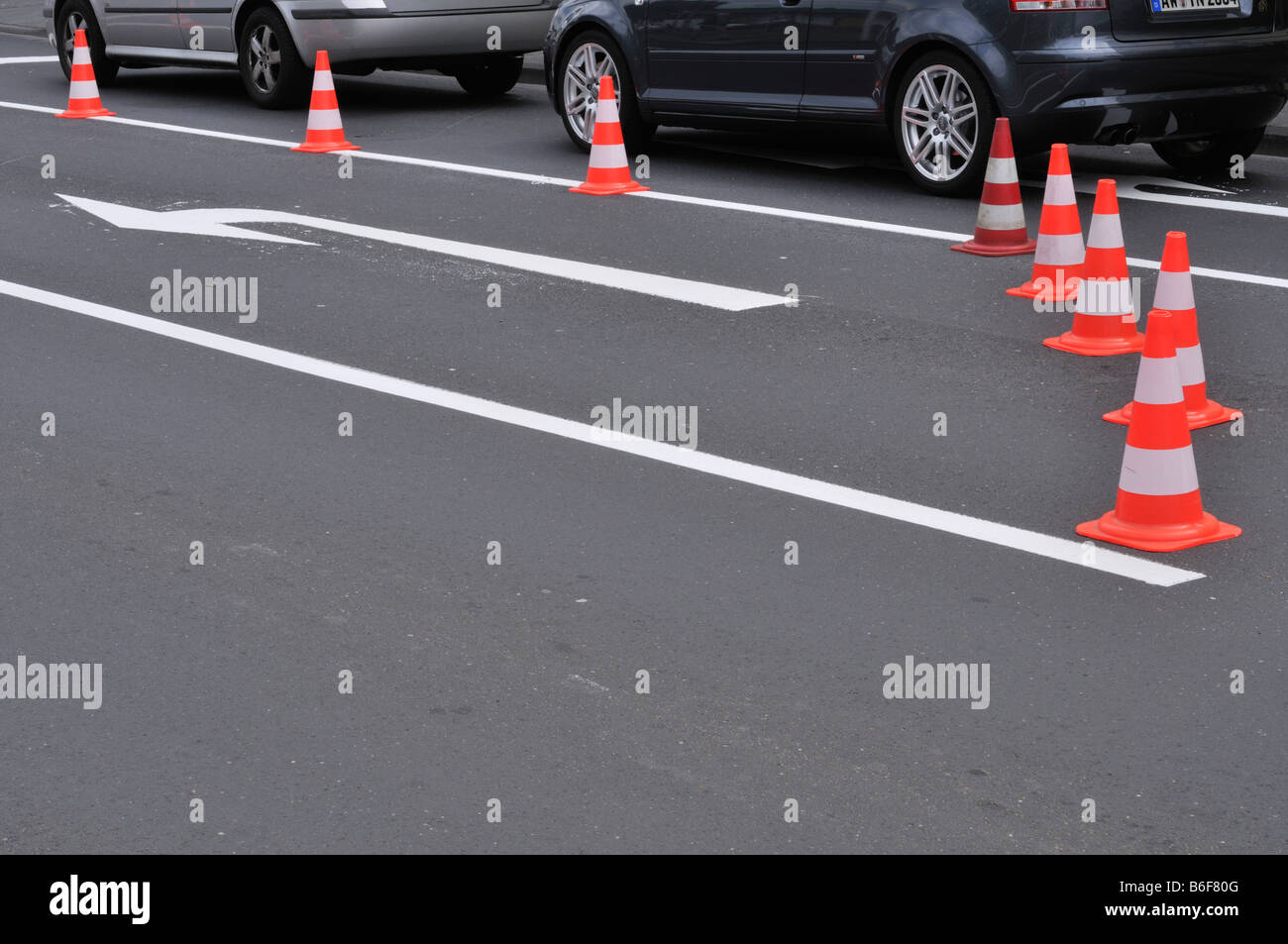 Coned off, Luebecker Huetchen, closed freshly marked turn, off lane, behind it stand 2 cars at stop line Stock Photo